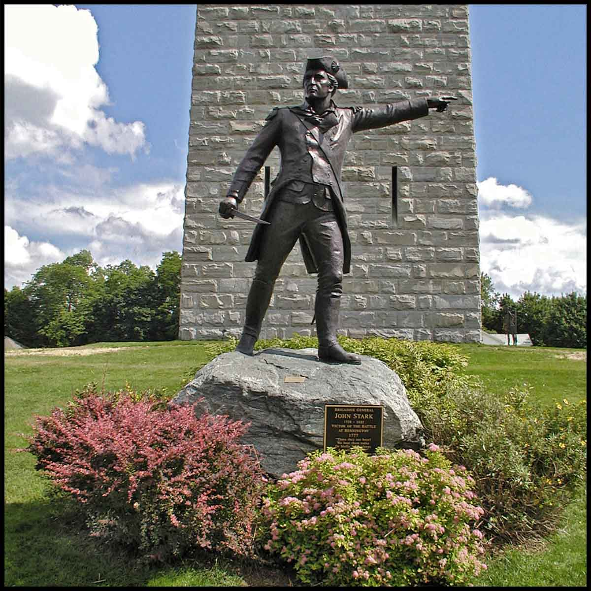 exterior photo of bronze sculpture of John Stark pointing with outstretched arm and standing on rock surrounded by shrubs in front of a obelisk-type monument