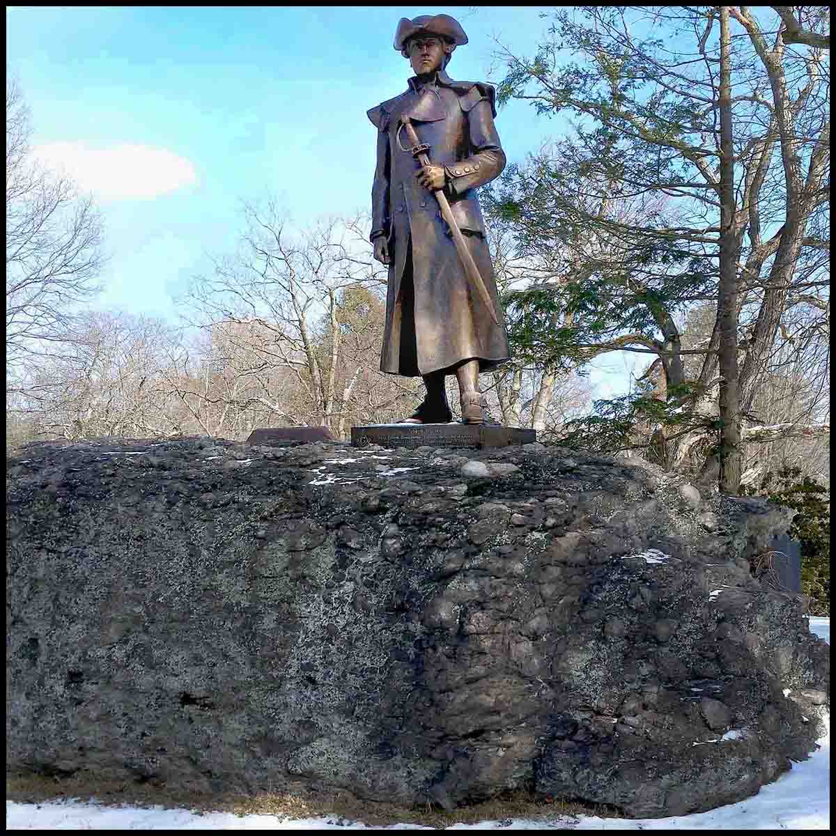 photo of bronze statue of Joseph Warren in uniform holding sword hilt at his side atop a large puddingstone