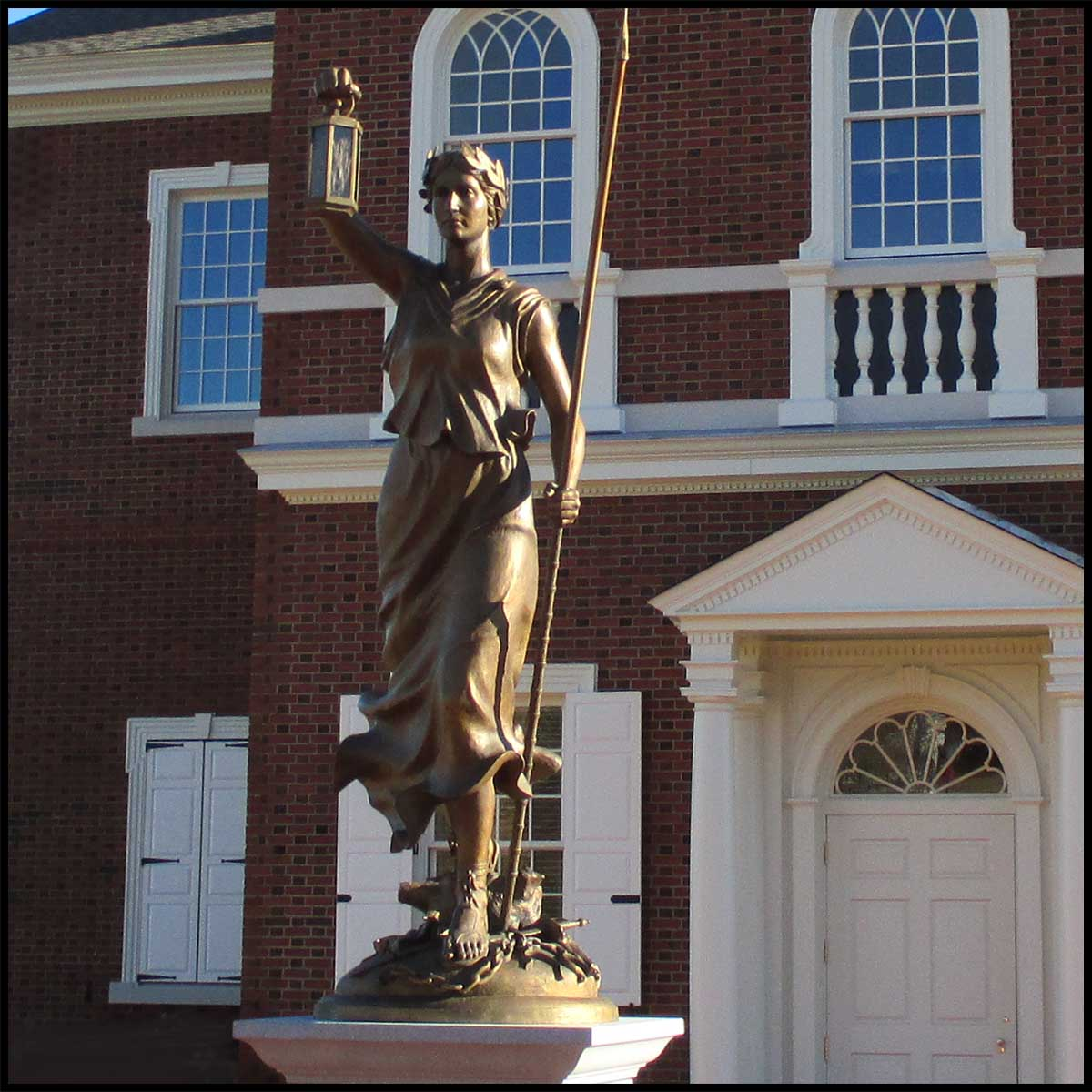 photo of bronze statue of female representing Liberty with arm raised and holding lantern in front of a brick building