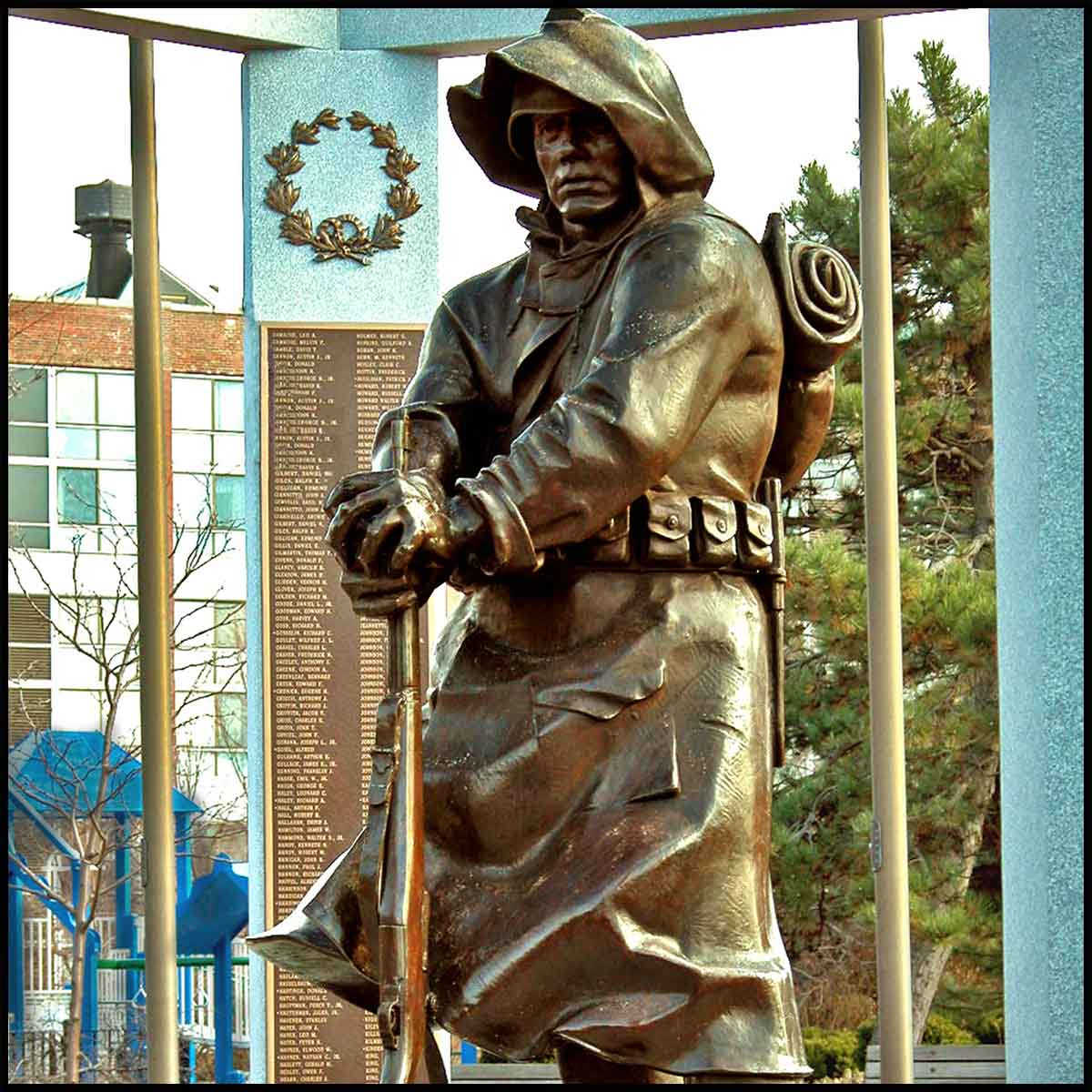 photo of bronze sculpture of male American soldier wearing hood and holding rifle at one end and resting it on ground surrounded by granite gazebo