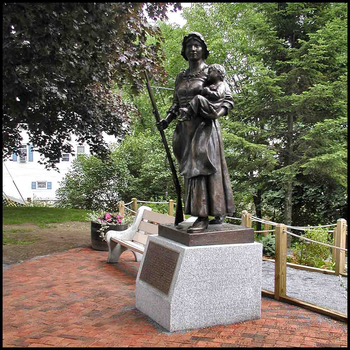 photo of bronze statue of Molly Stark holding child and musket atop stone base with plaque on a brick plaza with surrounding trees