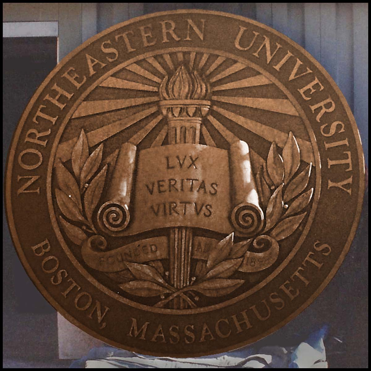 photo of bronze relief sculpture of Northeastern University's seal leaning up against wall