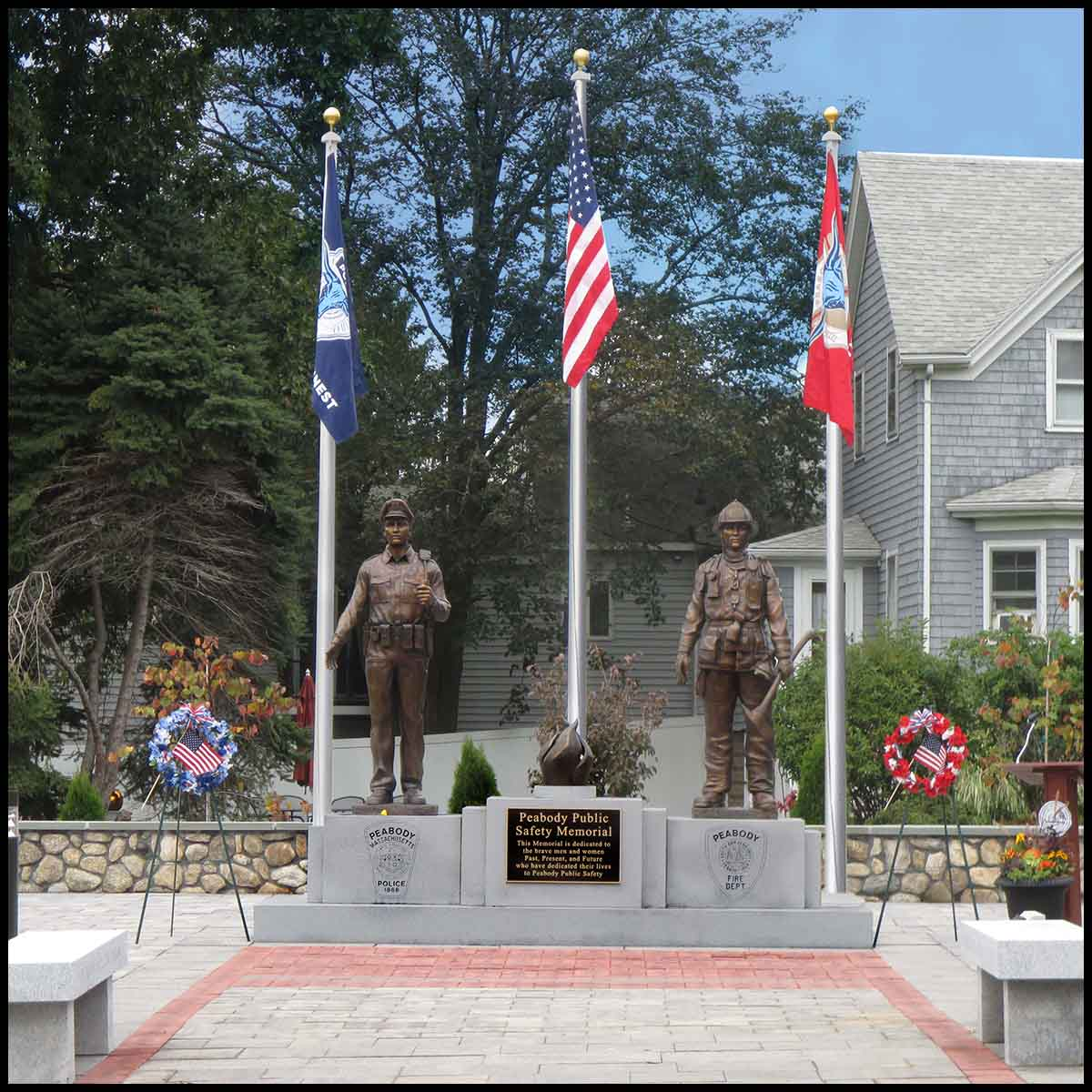 photo of outdoor memorial of bronze sculptures of a firefighter, a police officer, and an eternal flame on a large stone base with etchings and a bronze plaque in a paved site with three flags behind and trees and building behind