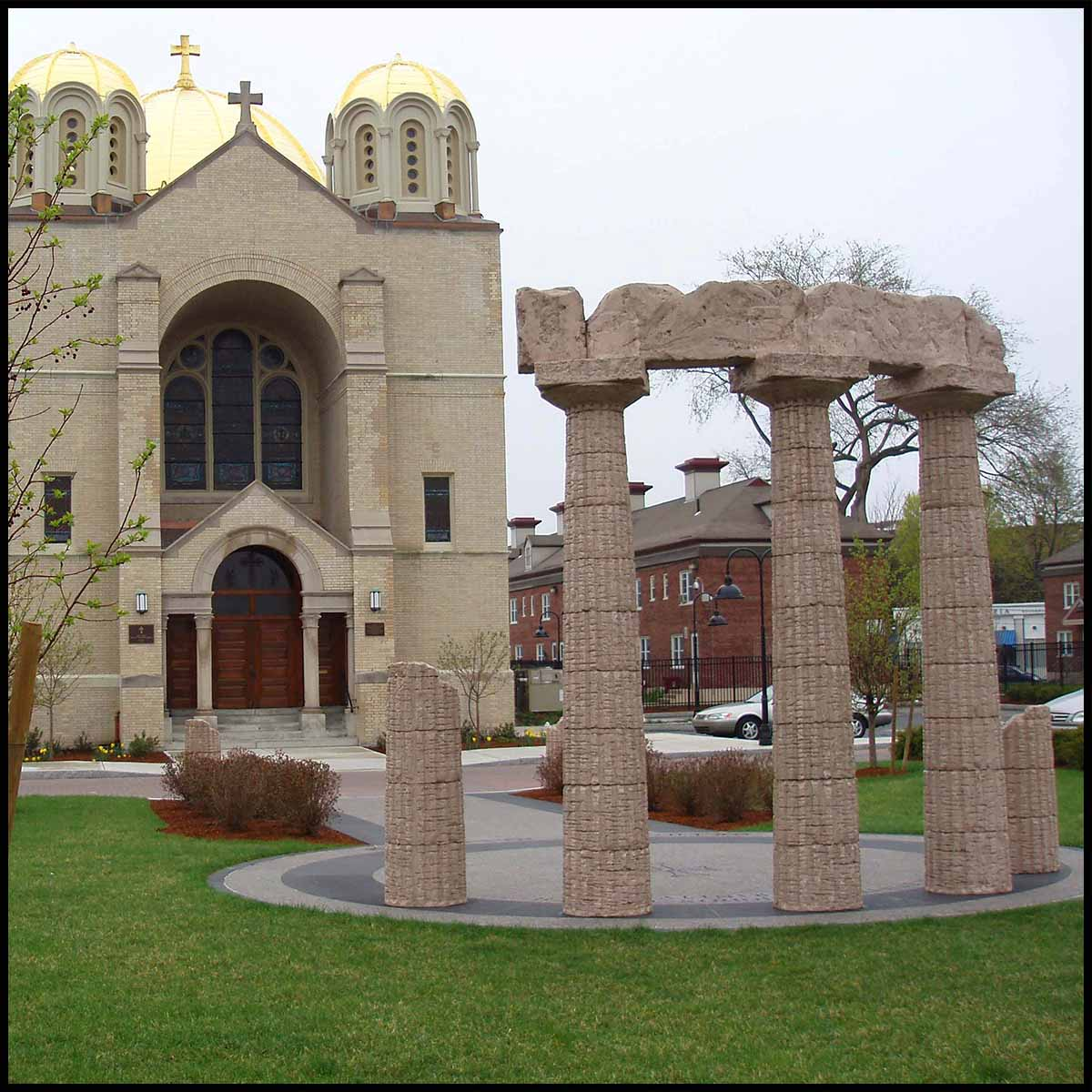 photo of church grounds with sculpture of ancient Greek temple ruins in front of stone church with gold domes
