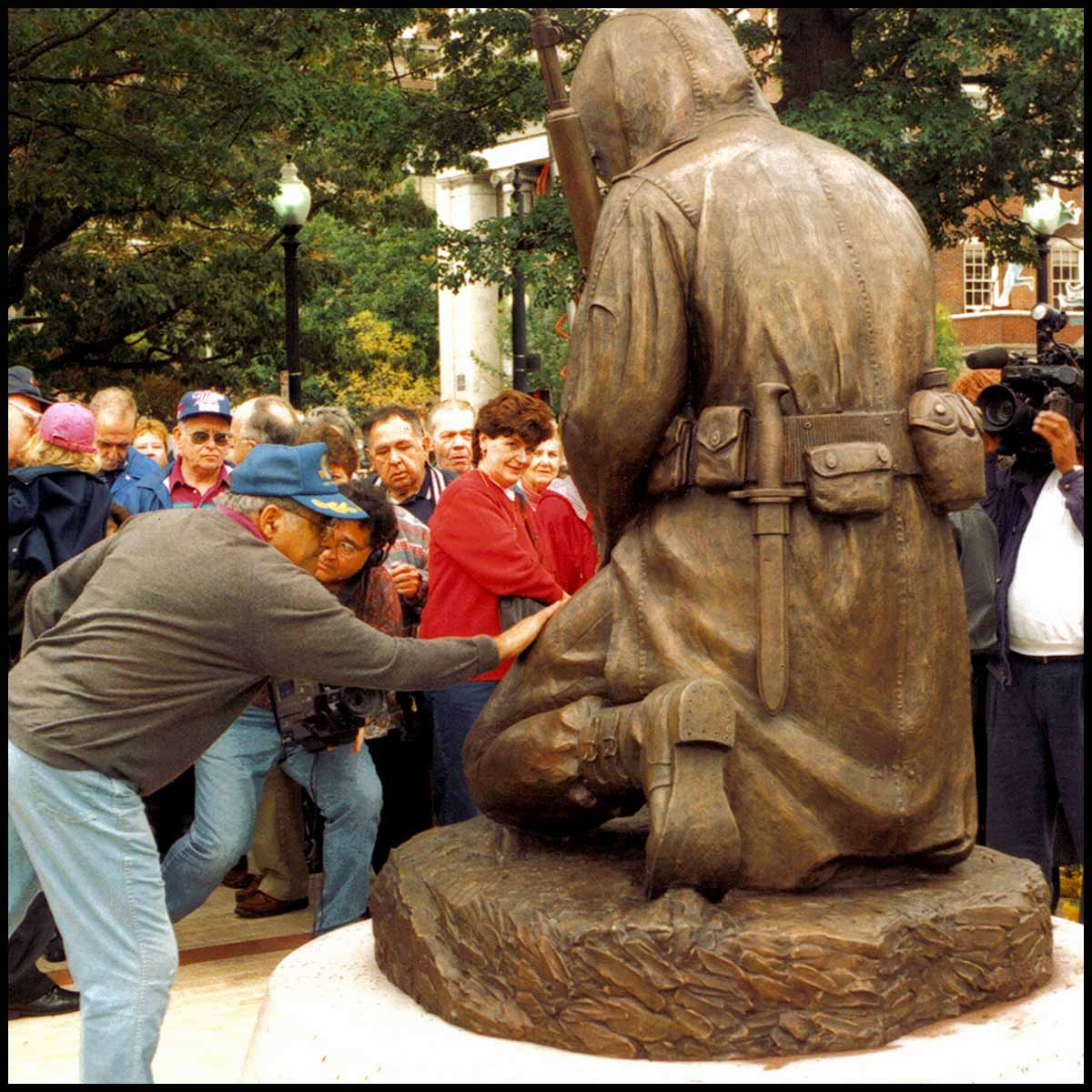 photo of man laying hand on bronze sculpture of kneeling Korean War soldier viewed from the back with crowd surrounding them and trees and buildings in background