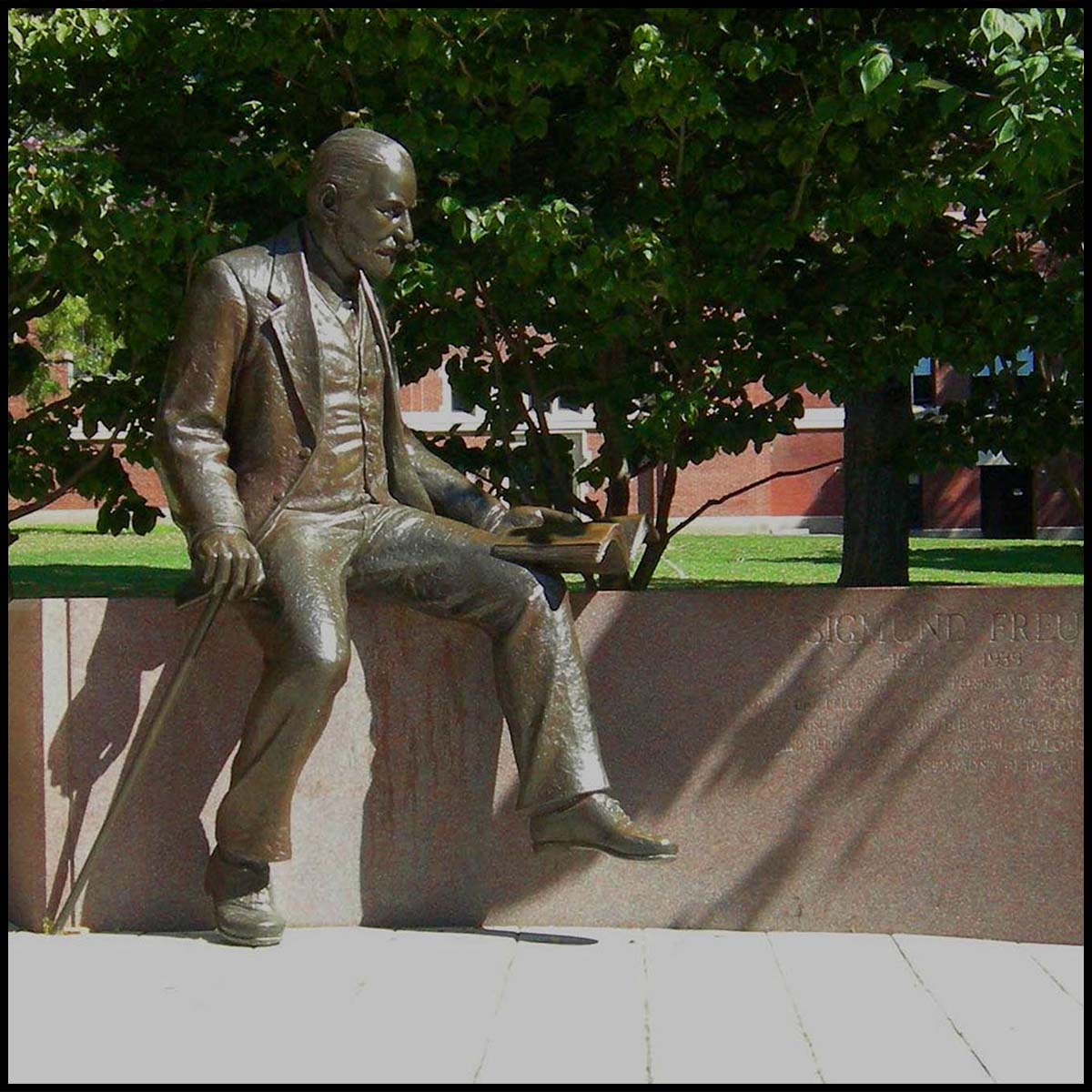 photo of bronze sculpture of Sigmund Freud sitting on a stone bench in a plaza with trees and grass behind