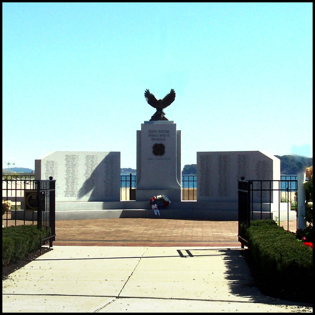 photo of granite monument with bronze eagle sculpture atop central piece in plaza