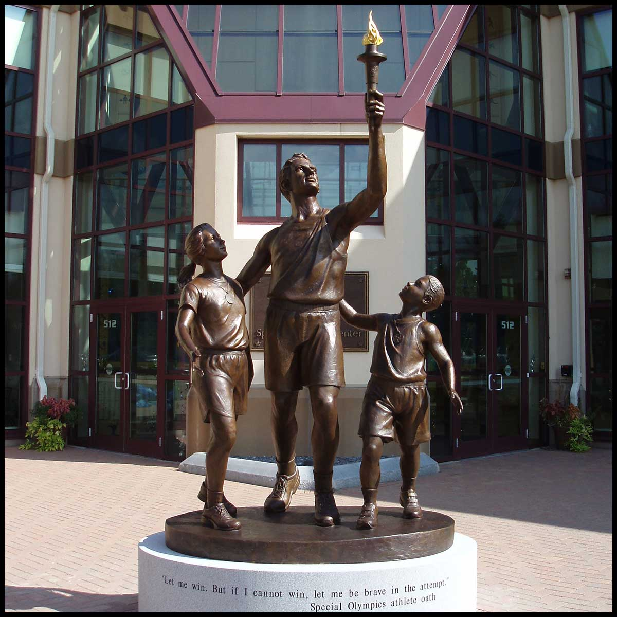 photo of bronze sculpture of man holding up Olympic torch with a boy and girl at his sides, placed on round stone base in plaza in front of building
