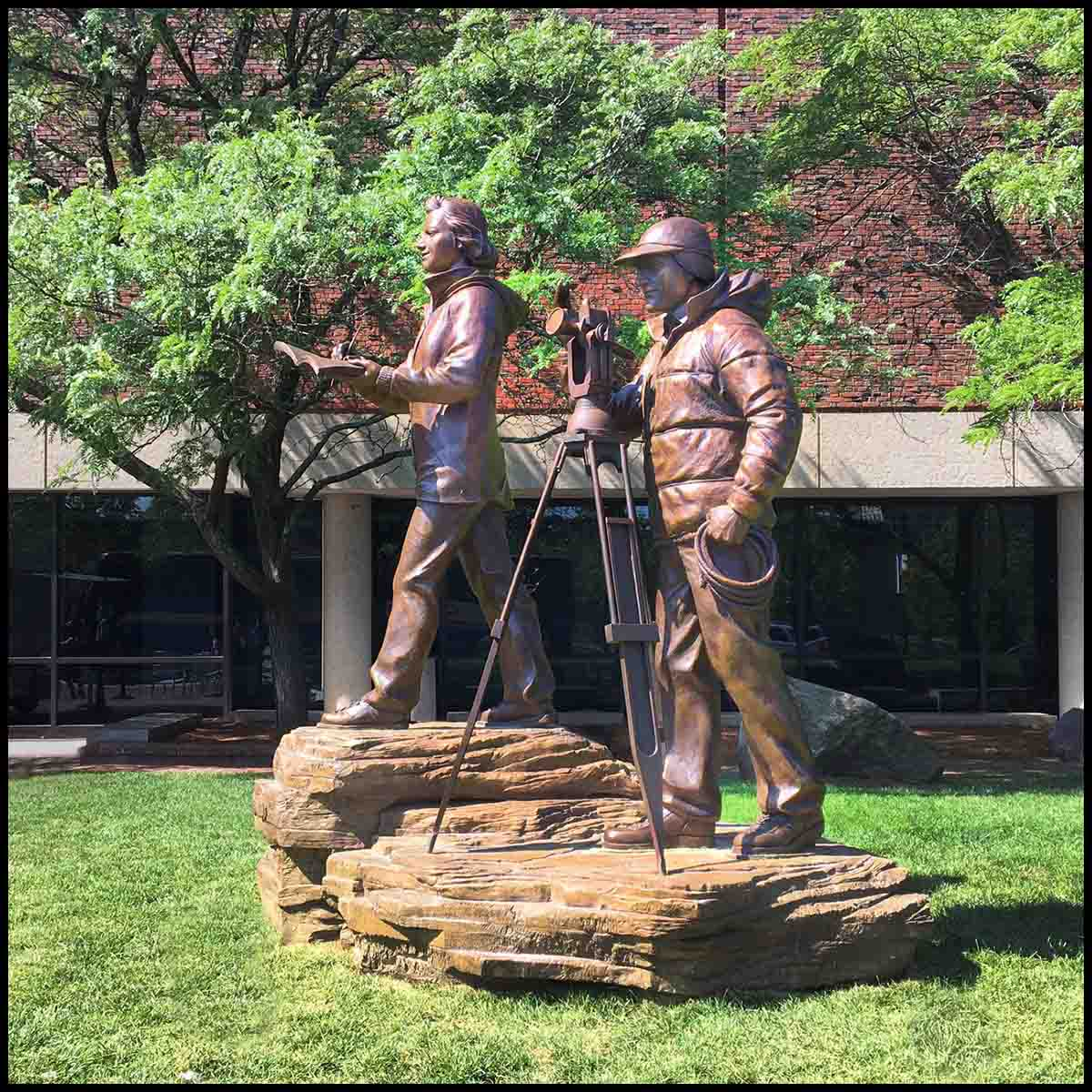 photo of bronze sculpture of man and woman in winter gear with theodolite on tripod and woman taking notes, standing on rock surface in front of a building on a green lawn