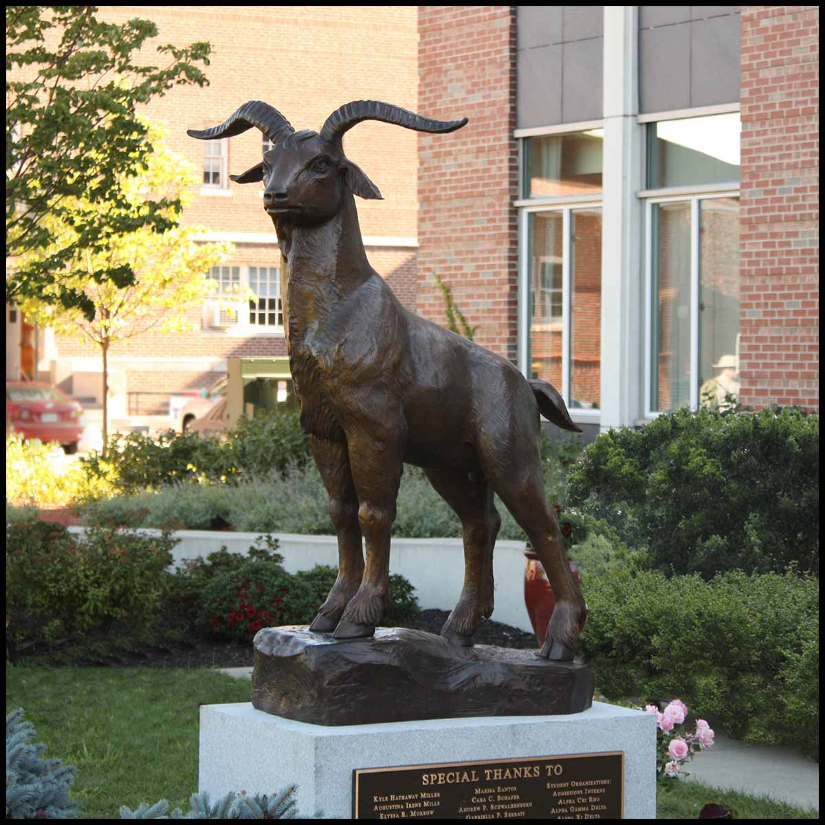 photo of bronze sculpture of goat standing on sculpted incline on granite base surrounded by greenery and brick buildings