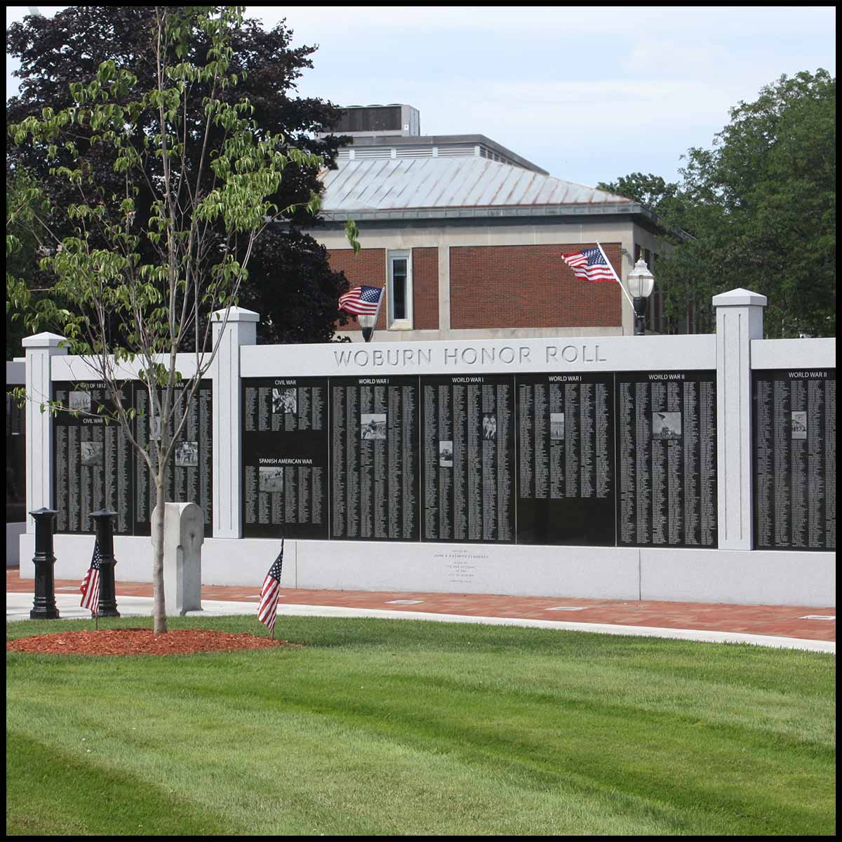 photo of black and gray granite monument in form of a wall in city green with building and trees behind