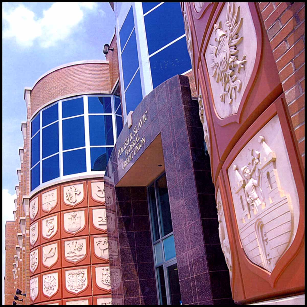 photo of entrance of stone and brick building with rounded tower-like elements and a series of white shields sculpted in relief set in brick-colored squares