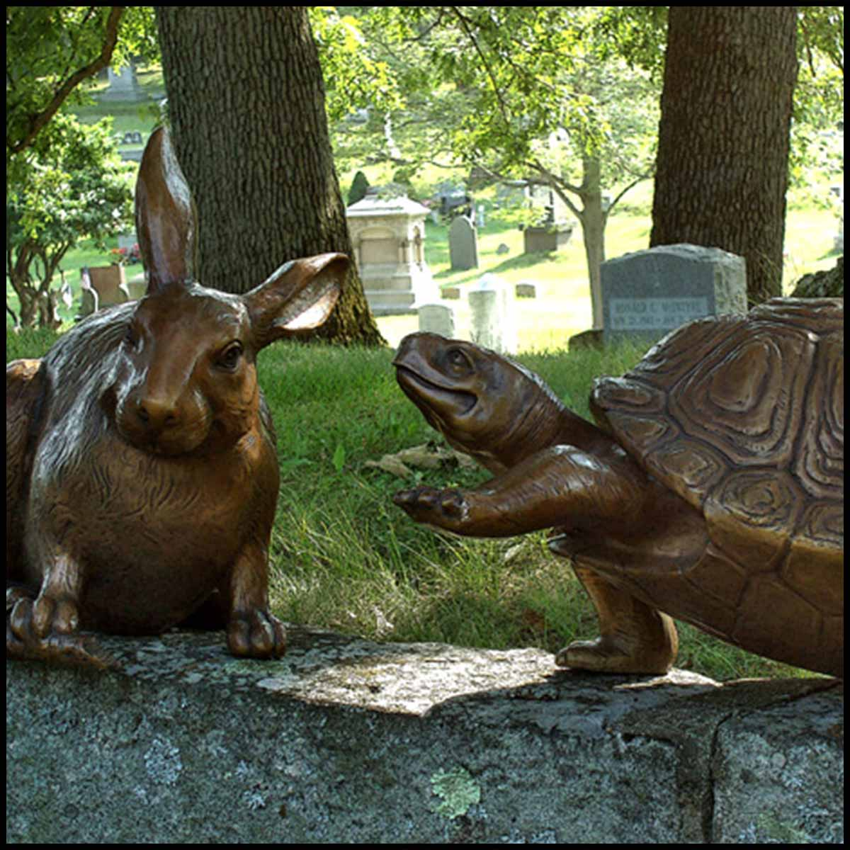 photo of bronze rabbit sculpture and bronze turtle sculpture sitting on a rock wall with grass and trees in the background