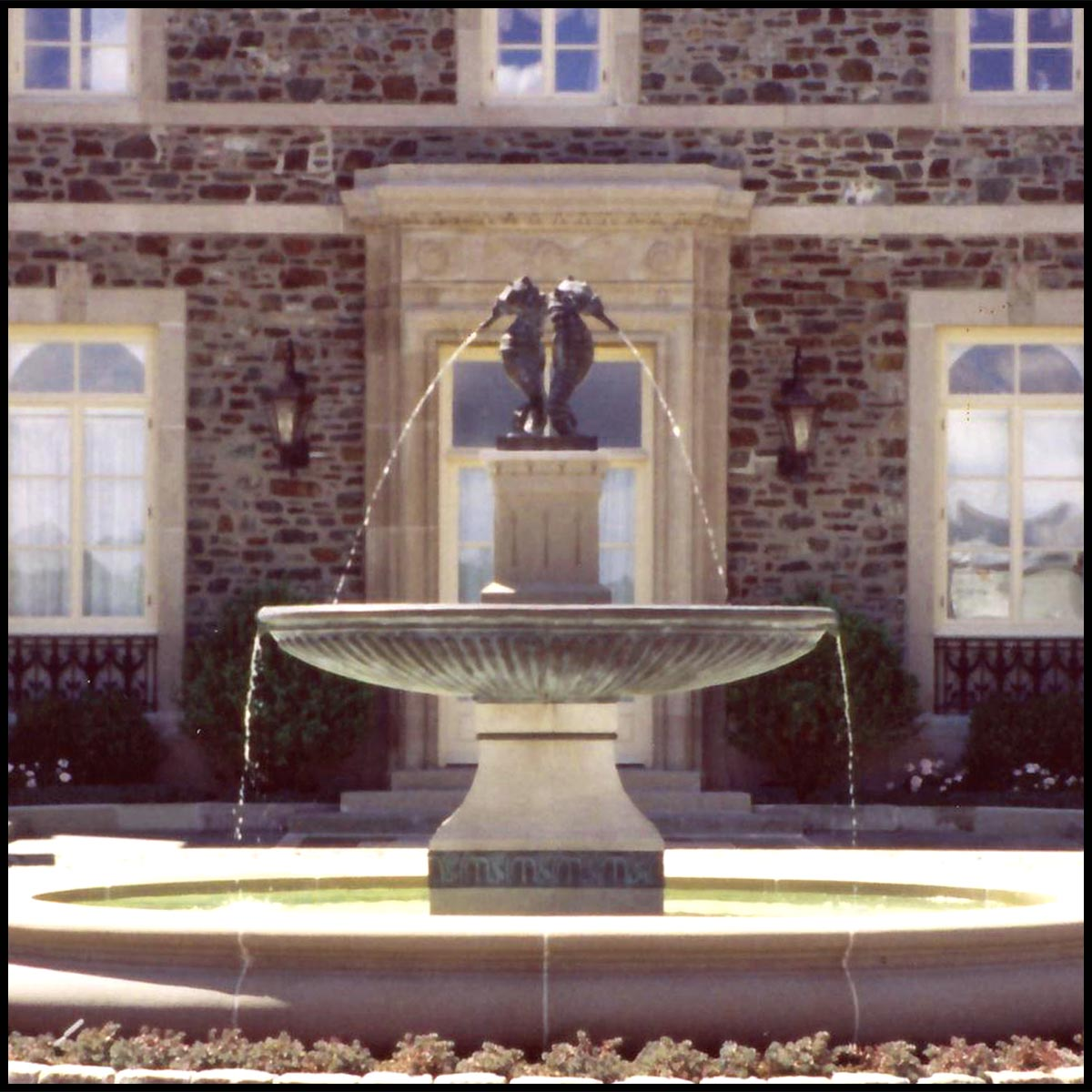 photo of granite fountain topped with bronze sculpture of two seahorses spouting water in front of a brick house