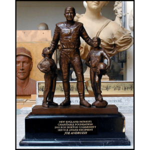 photo of bronze-colored sculpture of Rob Burton in football gear with a child on either side atop a black stone base with a plaque