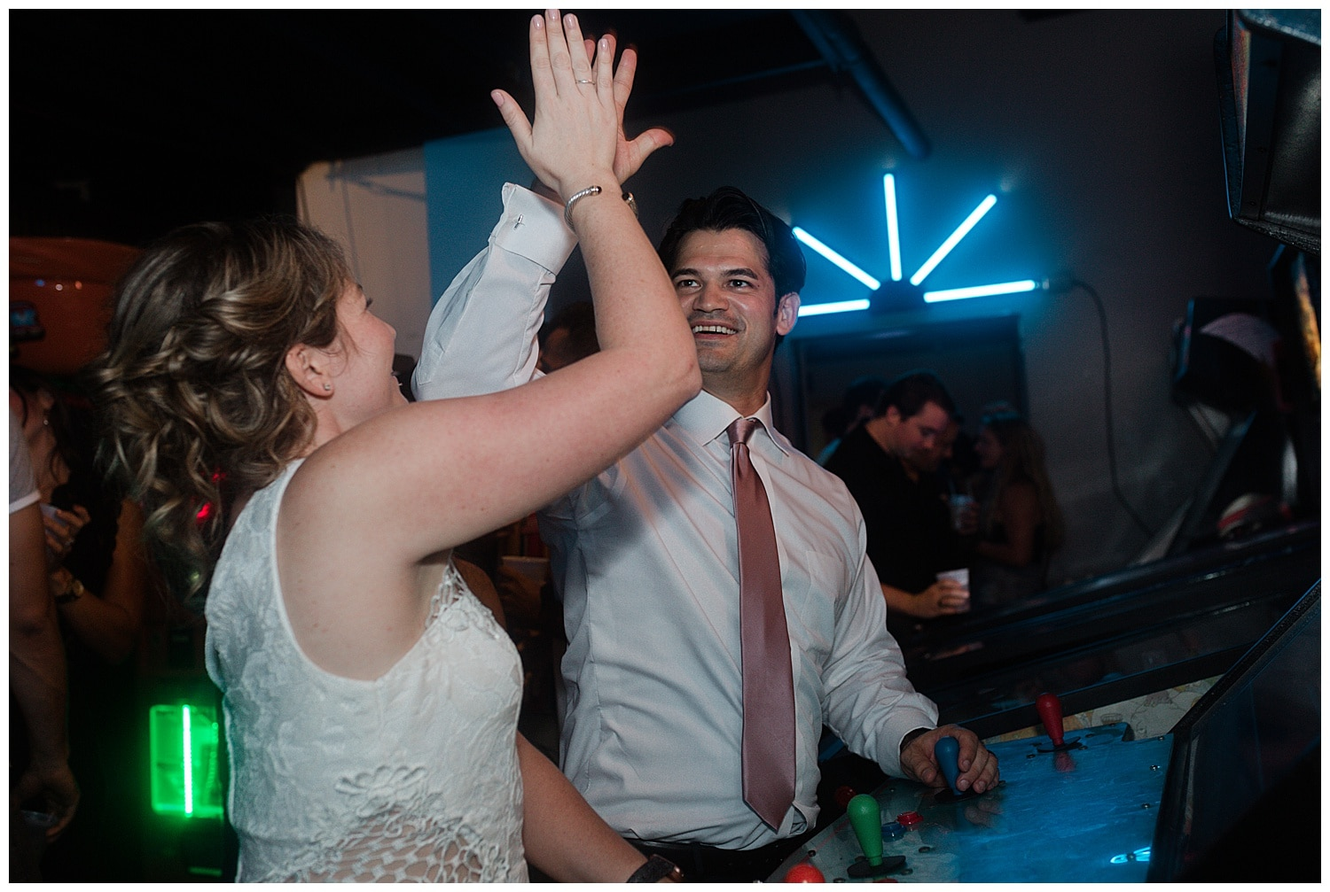 bride and groom arcade playing at an arcade night club in New Orleans by Swish and Click Photography