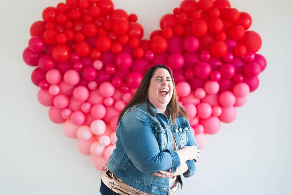 Christine Wright of Swish and Click Photography laughing in front of a heart balloon wall, is Houston's premier Harry Potter wedding photographer