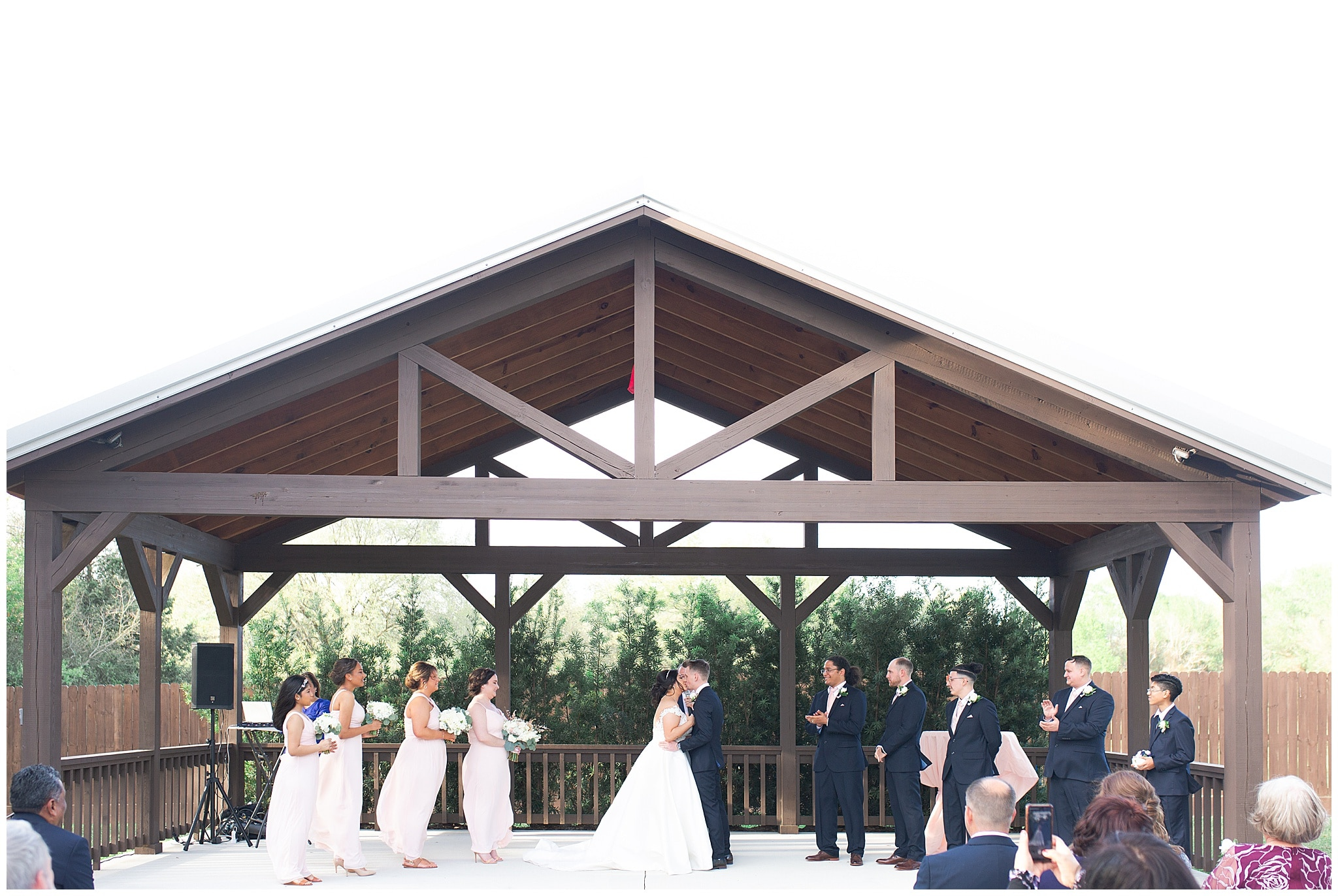 bride and groom first kiss at Bridal Oaks in Cypress Texas by Houston wedding photographer Swish and Click Photography