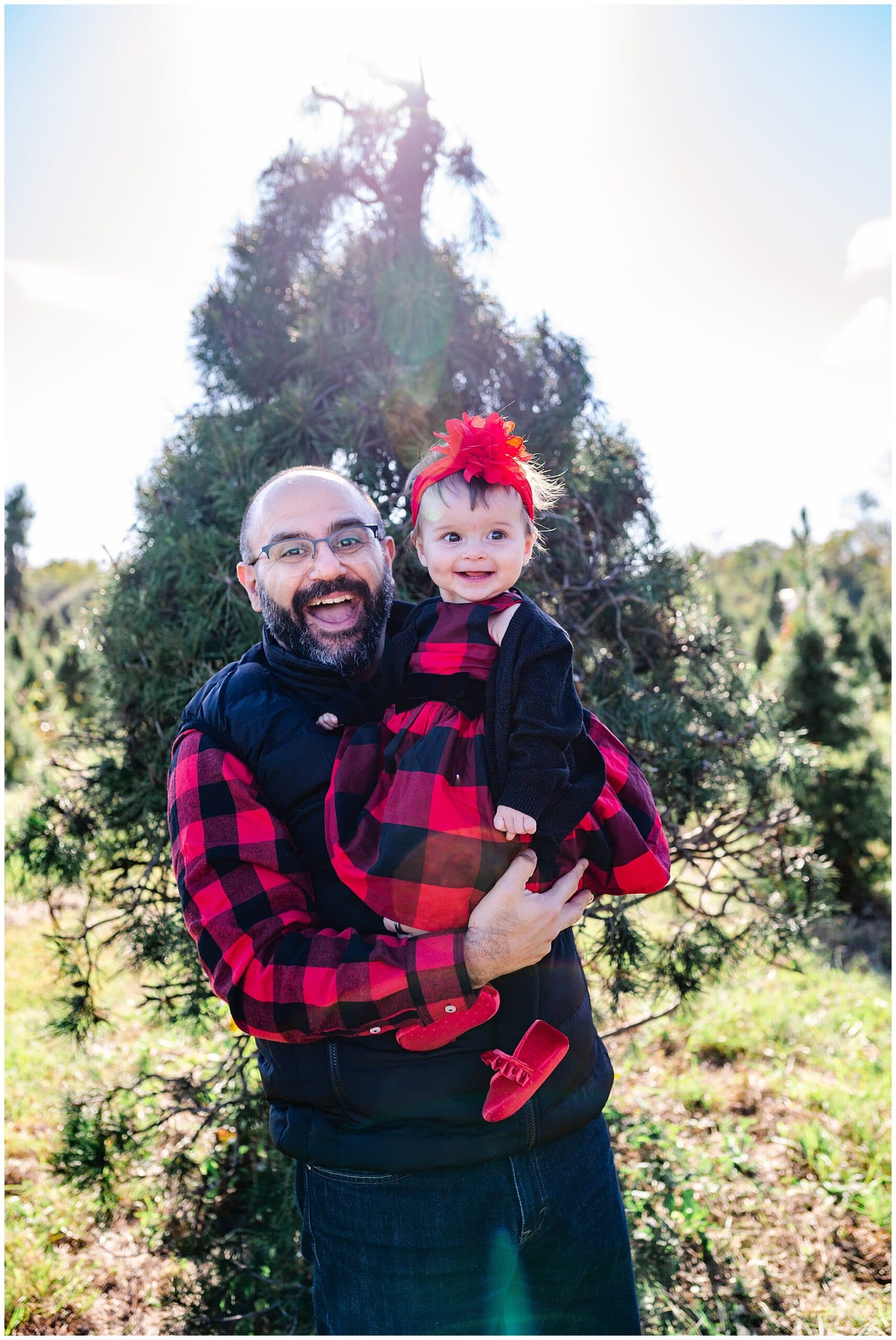 husband and baby posing at Christmas tree farm for family portraits by Swish and Click Photography at Holiday Acres Farm in Manvel Texas