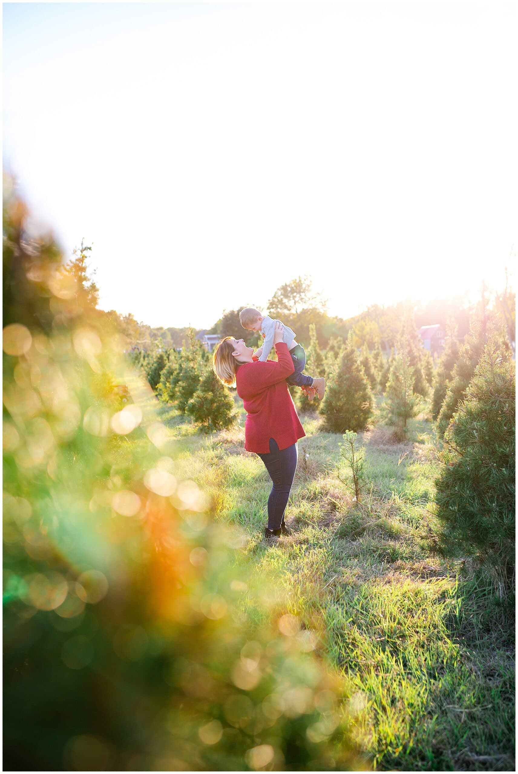 mom and son posing at Christmas tree farm for family portraits by Swish and Click Photography at Holiday Acres Farm in Manvel Texas