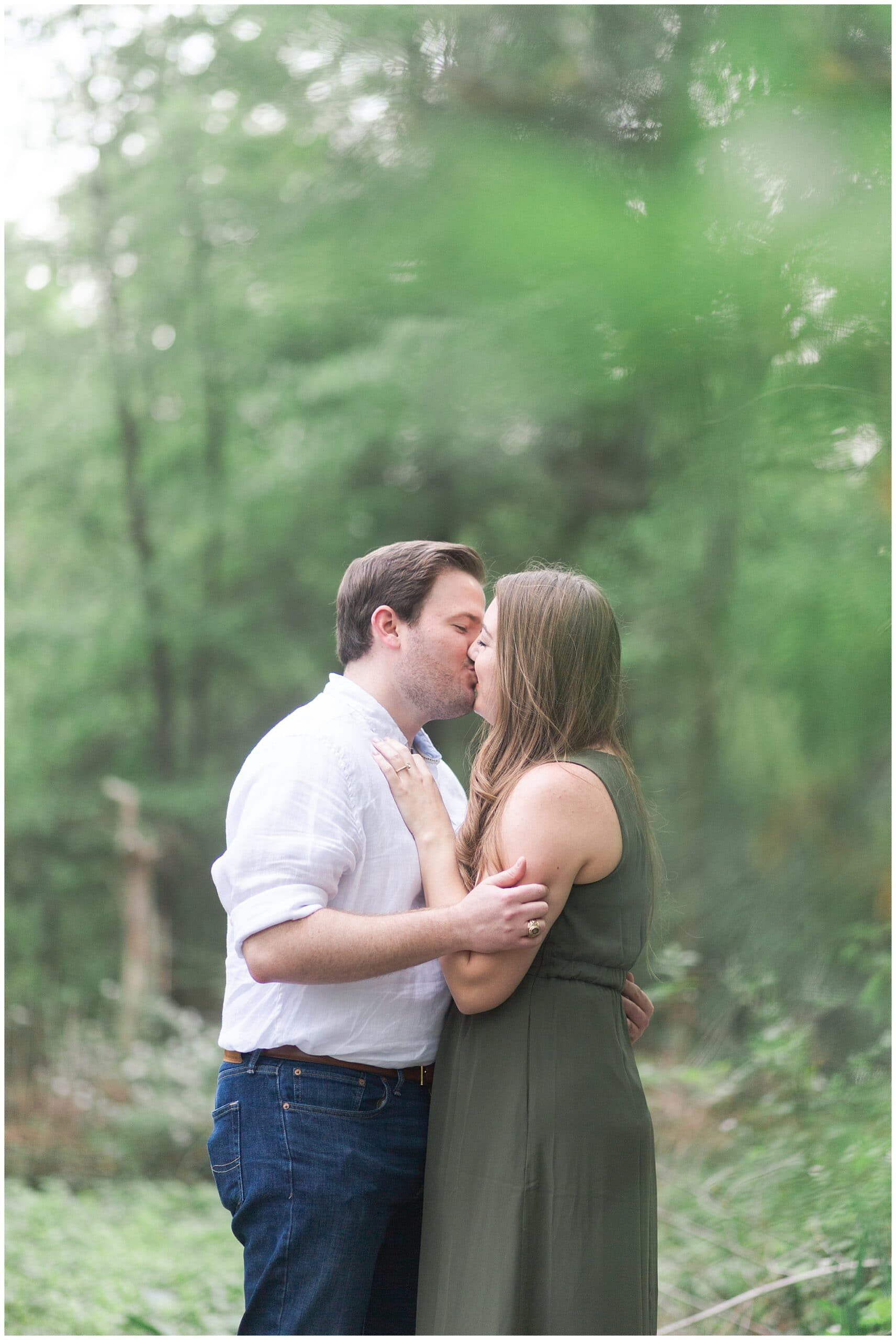 couple kissing in Houston Arboretum and Nature Center during their engagement session by Swish and Click Photography