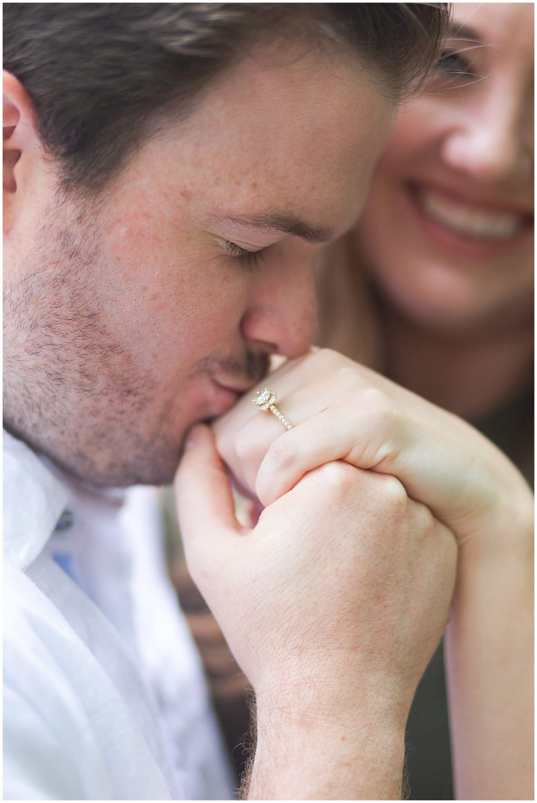 groom kissing engagement ring in Houston Arboretum and Nature Center during their engagement session by Swish and Click Photography