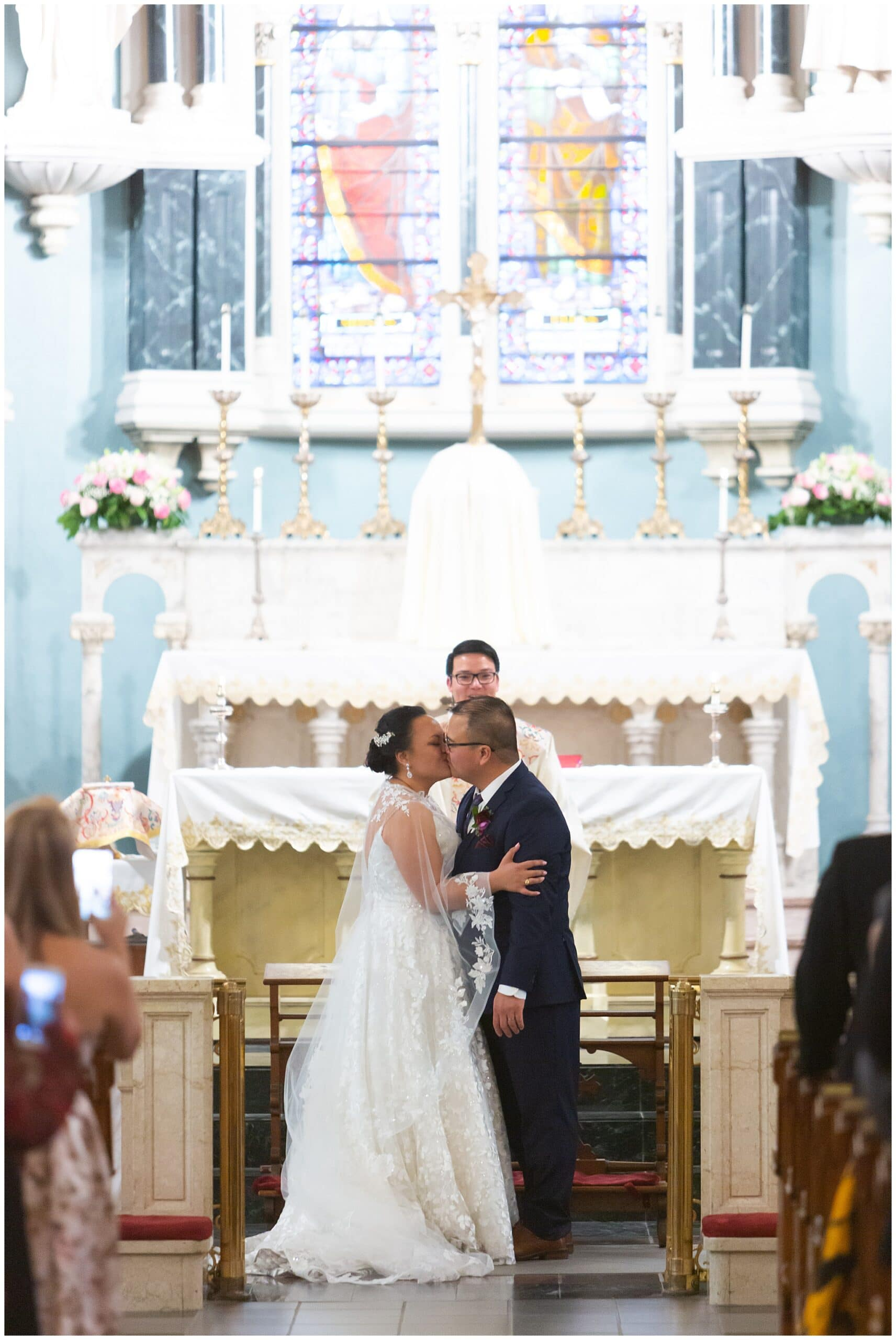 couple has first kiss at the end of their wedding ceremony at Annunciation Catholic Church in Houston TX by Swish and Click Photography