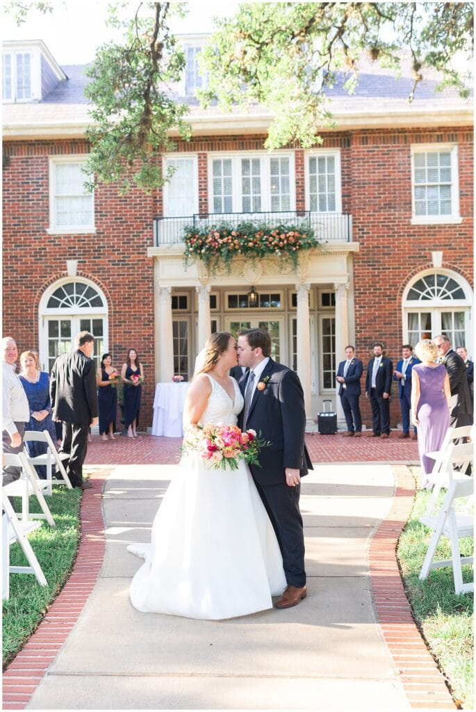 first kiss at wedding ceremony at Astin Mansion in Bryan Texas by Swish and Click Photography