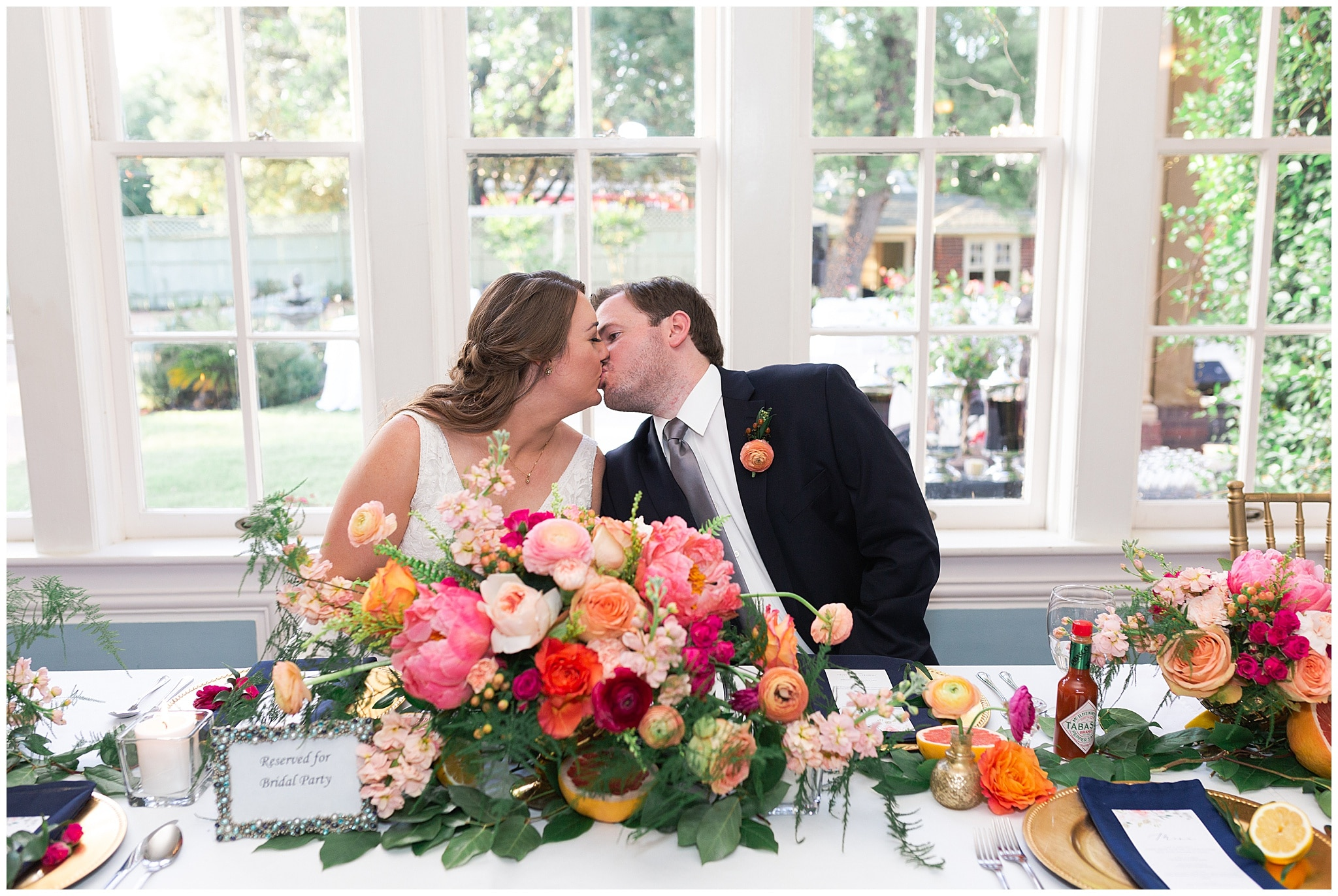 bride and groom kissing at their table at Astin Mansion in Bryan Texas by Swish and Click Photography