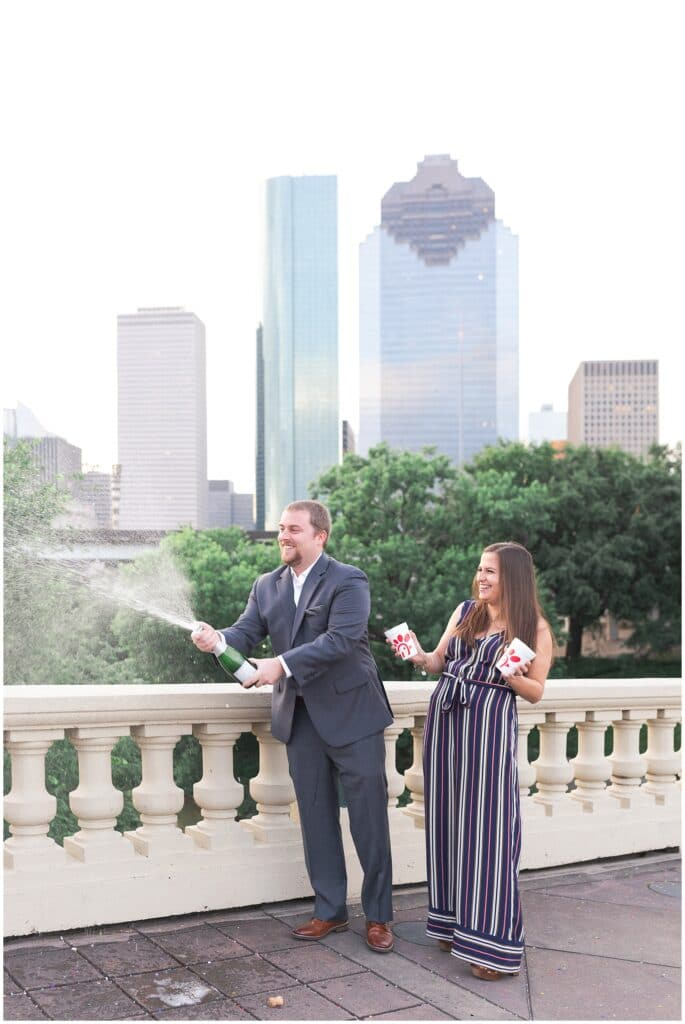 couple popping champagne on Sabine St bridge during engagement session by Swish and Click Photography