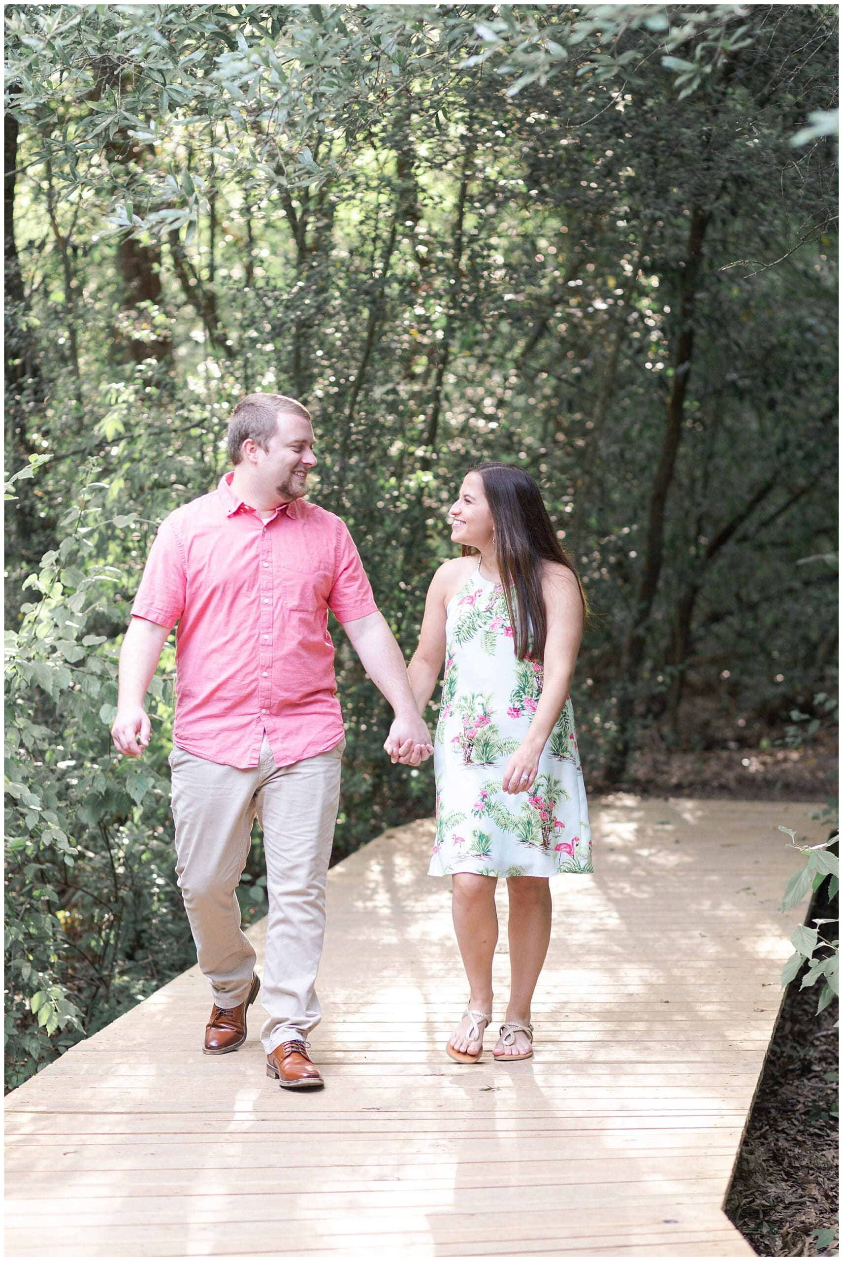 couple walking Houston Arboretum during engagement session by Swish and Click Photography