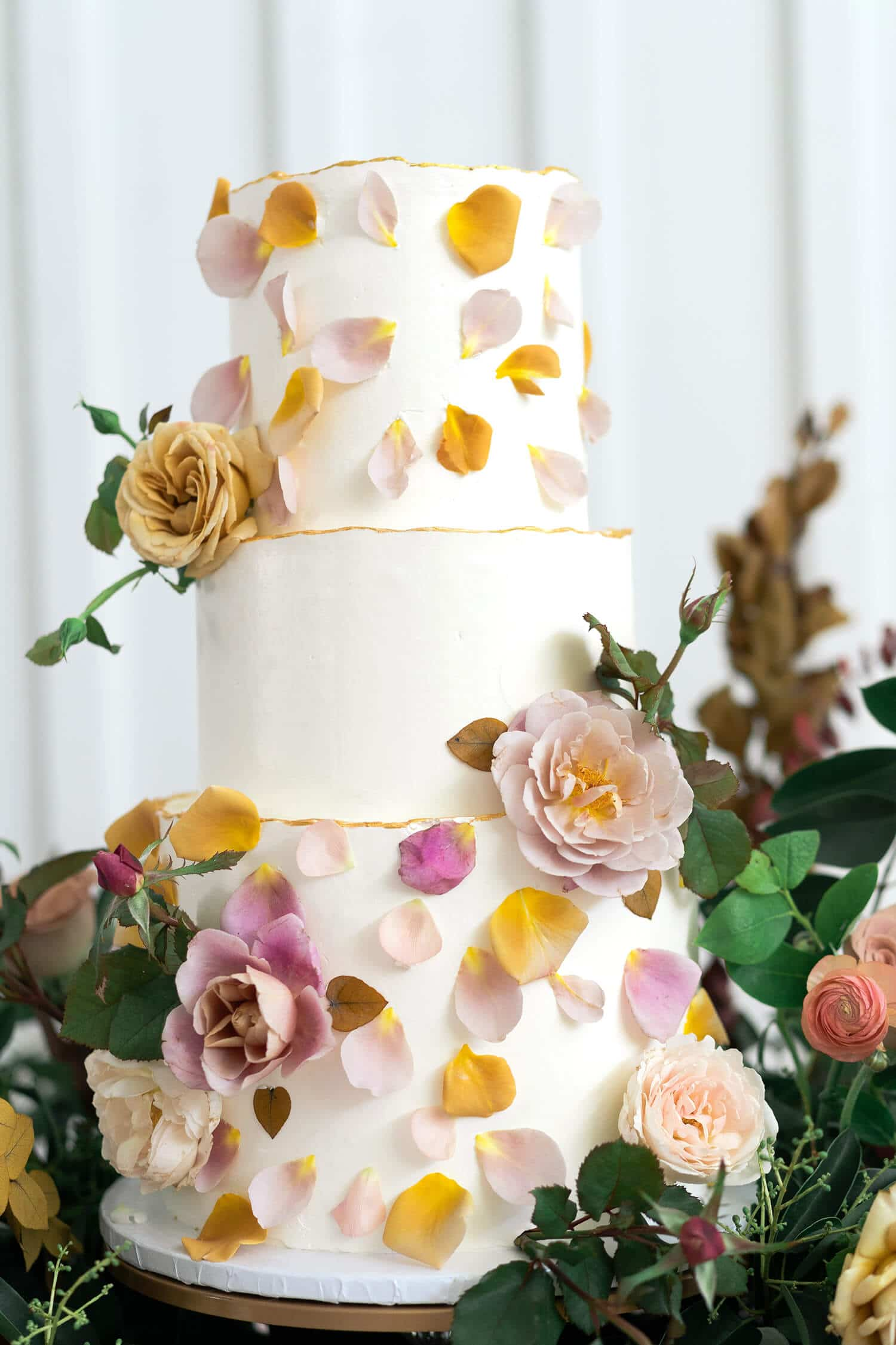 wedding cake adorned with rose petals at The Farmhouse in Montgomery Texas by Swish and Click Photography 15 essential questions