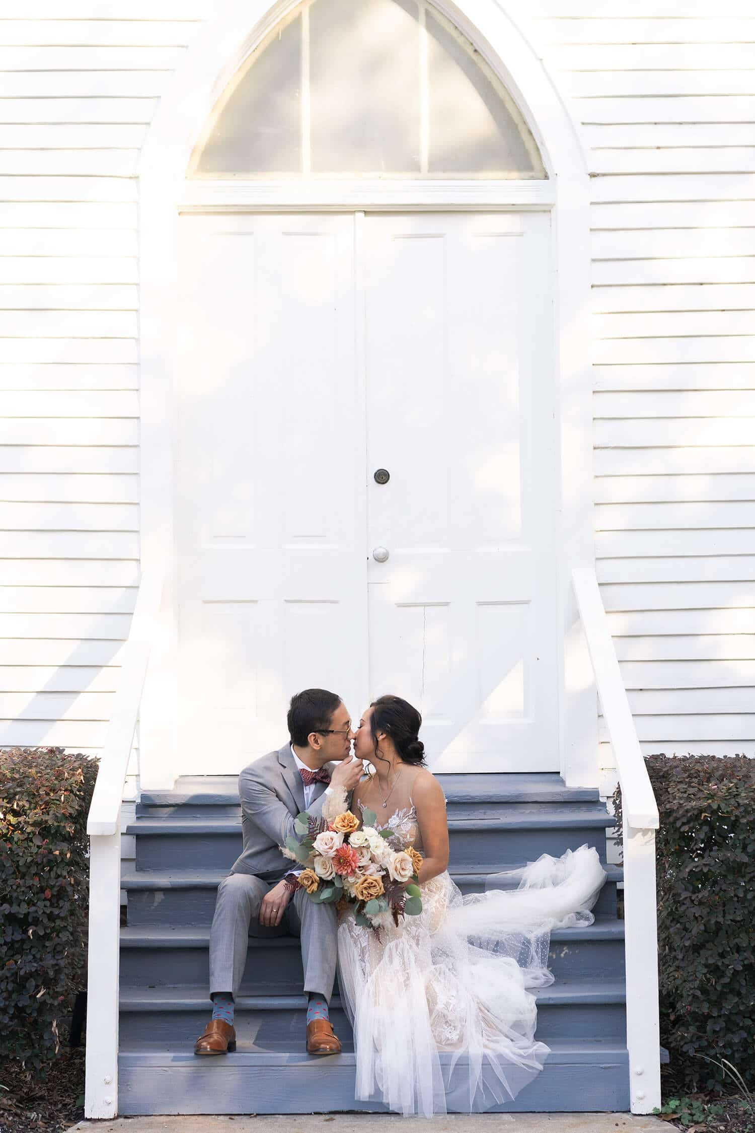 couples kisses on the steps of a Houston church at Sam Houston Park by Swish and Click Photography