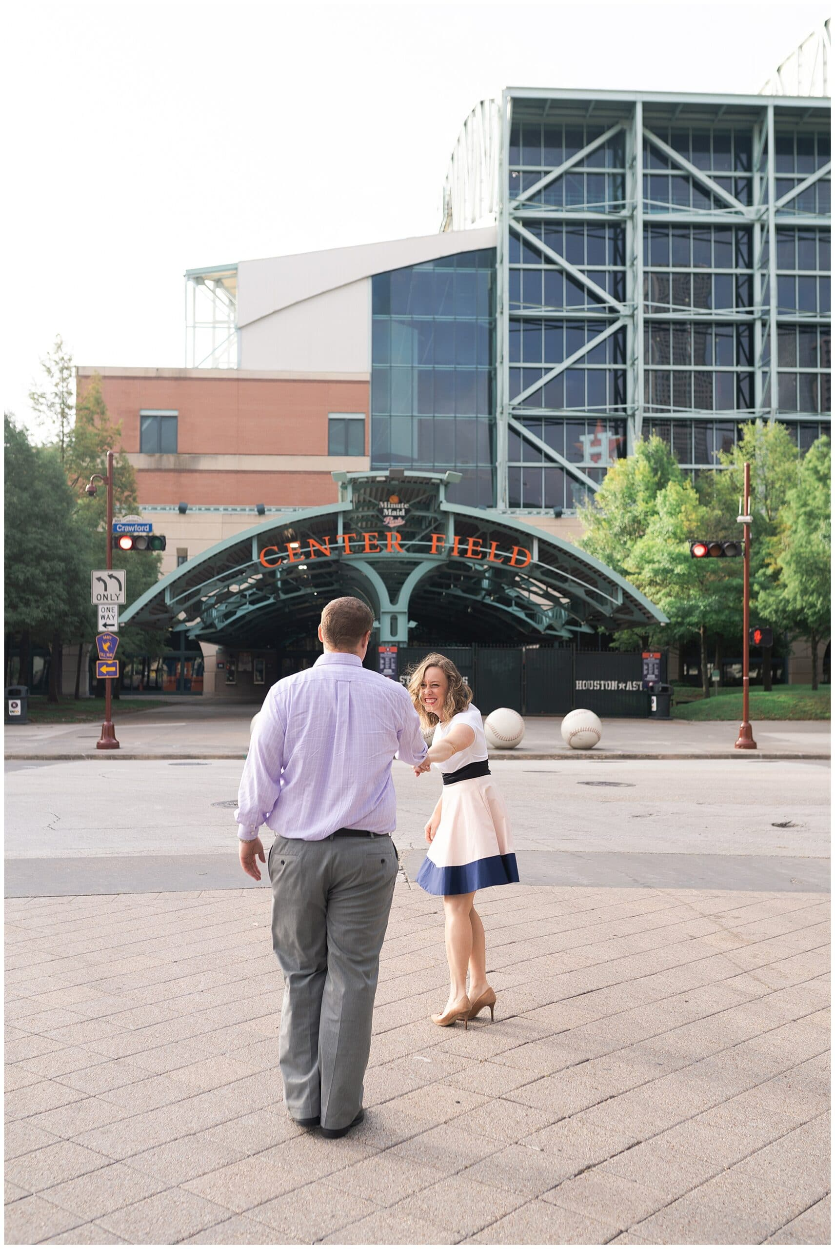 engaged couple walk outside Astors Minute Maid Park in downtown Houston by Swish and Click Photography