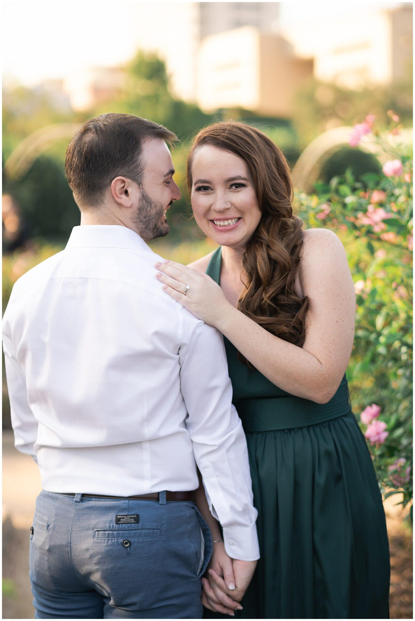 engaged couple snuggle during their engagement session at McGovern Centennial Gardens in Houston Texas captured by Swish and Click Photography
