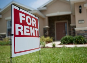 A picture of a for rent sign in front of a house.