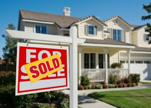 A picture of a sold sign in front of a house.