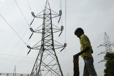 A man stands in front of an electric pylon installed at a power house in Allahabad