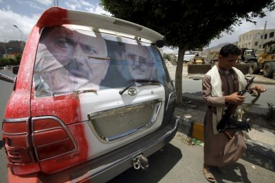 A man with carrying a weapon walks past a car adorned with a poster of Yemen's former President Ali Abdullah Saleh in Yemen's capital Sanaa