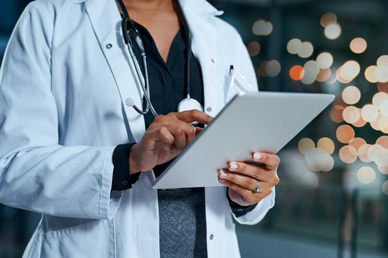 person in lab coat with tablet