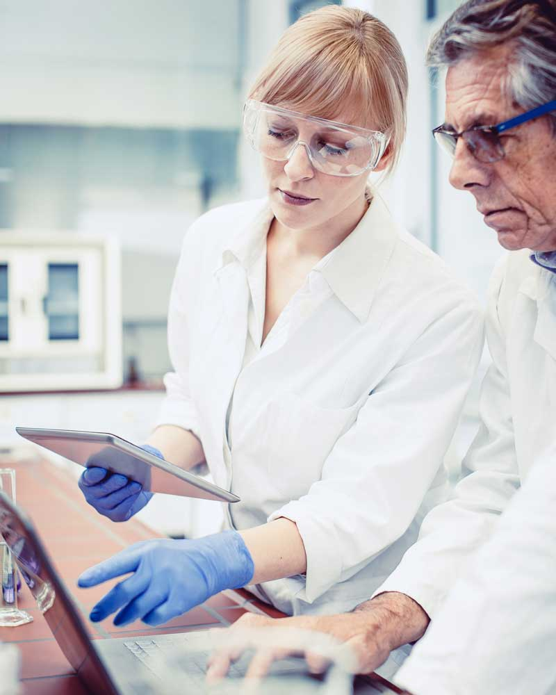 two scientists in lab working on computer and tablet