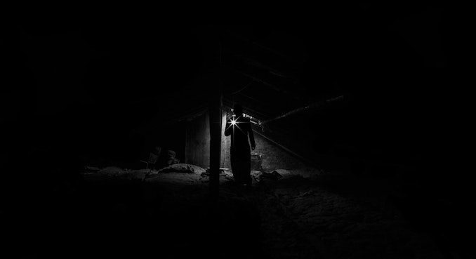 man in dark with flashlight