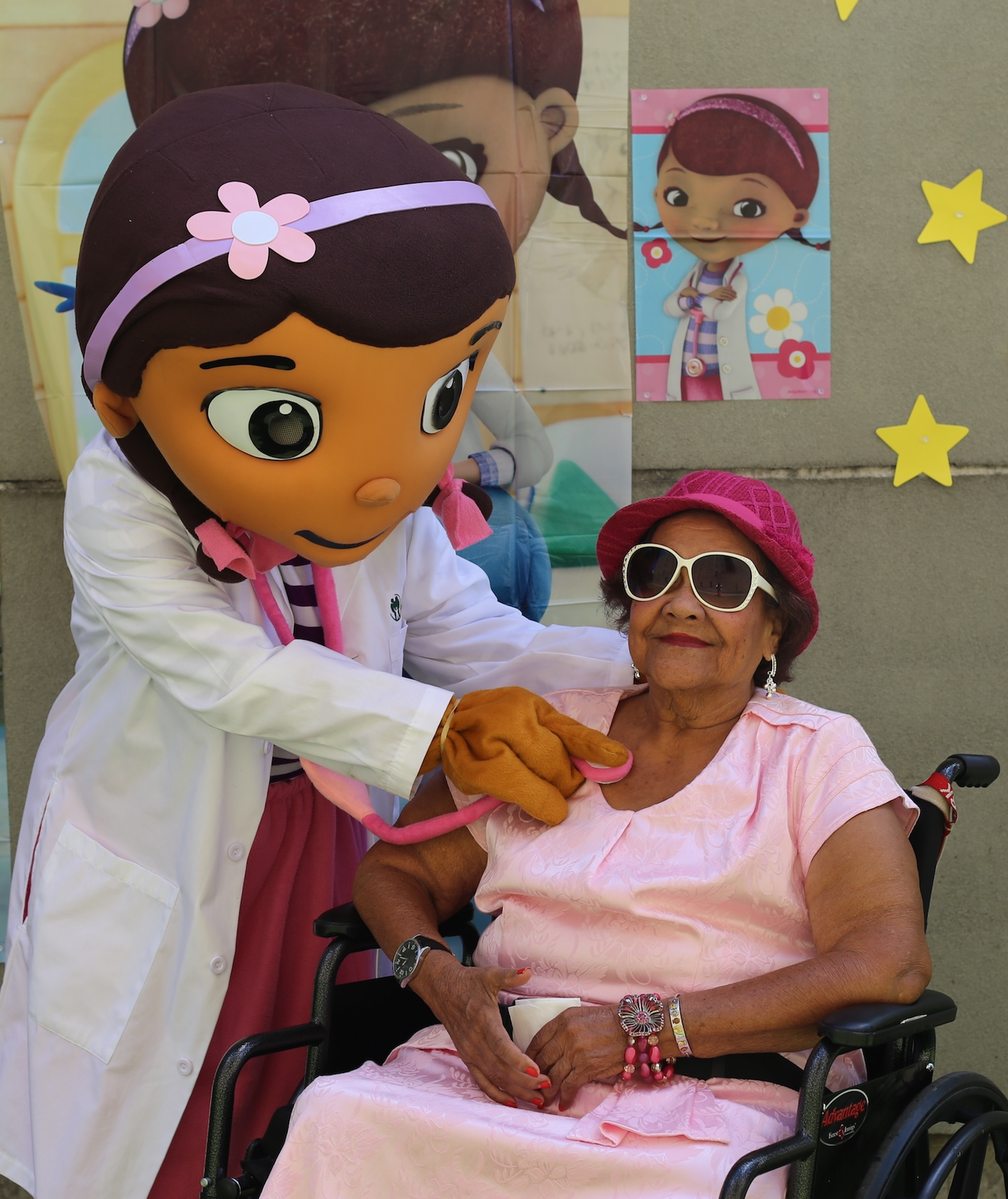 """A costumed """"doctor"""" uses a stethoscope as an older patient in a wheelchair plays along."""