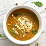 Creamy Tomato Soup with Ground Chicken and Spinach in a pot on counter with spoon and spinach leaves on counter. It