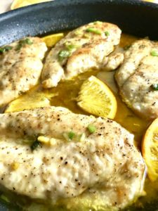 Close up of chicken cooked in pan with orange slices