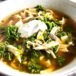 Chicken Tortilla Soup in a bowl with sour cream on top. It's quick, it's easy, it's delicious AND...it's an all-in-one balanced dish because I have added KALE! Done in 30 minutes!