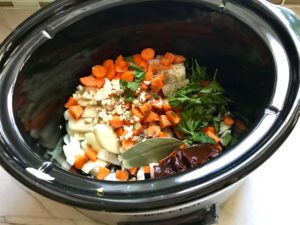 Short Ribs ingredients all added to the slow cooker: carrots, onions, demi-glace, bay leaf, parsley, garlic