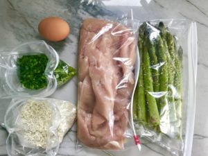 chicken, asparagus, breadcrumbs, scallions, and egg all in baggies on counter