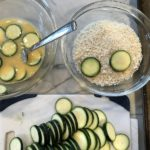 Dipping raw zucchini into egg and into breadcrumbs.