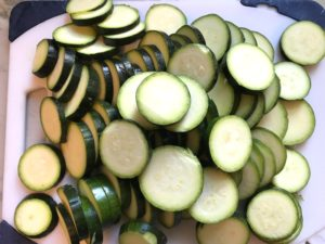 Raw slices of Zucchini on cutting board.